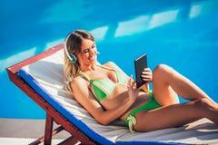 少妇画象热带太阳的在游泳池附近 库存照片