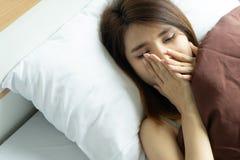 少妇疲倦的哈欠唤醒拿着闹钟 叫醒ea 图库摄影