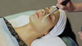 少妇的温泉疗法有化妆面具在美容院 应用巧克力面具于女孩` s面孔 股票录像