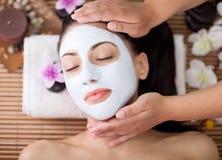 少妇的温泉疗法有面部面具在美容院 免版税图库摄影
