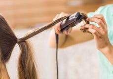少妇的美发师卷曲的头发 关于她的发型的女孩关心 免版税图库摄影