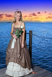 少妇的画象有一朵花的在反对海的手上在日落期间 免版税库存图片
