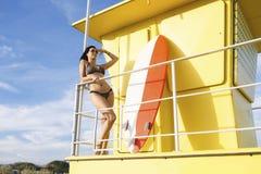 少妇的画象用手在看远离救生员房子的前额附近,当休息时在冲浪以后 库存照片