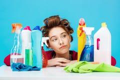 少妇看起来在桌后的疲乏的开会与清洁工具 免版税图库摄影