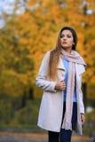 少妇秋天黄色槭树庭院背景 秋天美丽的公园妇女 室外纵向 美好的秀丽注视构成自然本质纵向妇女 库存照片