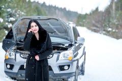 少妇等待的帮助或协助在她的汽车breakdo以后 免版税库存照片