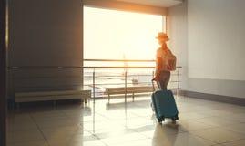 少妇等待的飞行在窗口的机场与suitcas 免版税库存图片