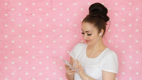 少妇给耳机穿衣并且使用在智能手机的应用听到从播放表的音乐概念  影视素材