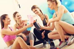 少妇编组休息在健身房在锻炼以后 库存照片