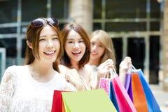 少妇编组在街道上的运载的购物袋 免版税库存图片