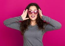 少妇美丽的画象,摆在桃红色背景,长的卷发,太阳镜在心脏塑造,魅力概念 库存图片