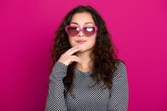 少妇美丽的画象,摆在桃红色背景,长的卷发,太阳镜在心脏塑造,魅力概念 免版税图库摄影