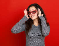 少妇美丽的画象,摆在红色背景,长的卷发,太阳镜在心脏塑造,魅力概念 图库摄影
