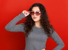 少妇美丽的画象,摆在红色背景,长的卷发,太阳镜在心脏塑造,魅力概念 库存照片