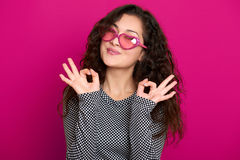 少妇美好的画象展示okay标志,摆在桃红色背景,长的卷发,太阳镜在心脏塑造,浓缩的魅力 库存图片
