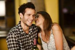 少妇耳语入她的男朋友的耳朵 免版税库存图片