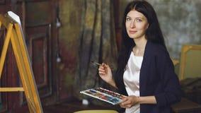 少妇艺术家与水彩油漆的凹道在画架帆布的pictrure和刷子 免版税库存图片