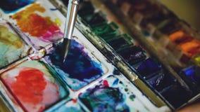 少妇艺术家与水彩油漆的凹道pictrure 在pallete的特写镜头刷子混合的颜色 免版税库存照片