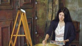 少妇艺术家与水彩油漆的凹道在画架帆布的pictrure和刷子 影视素材