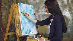 少妇艺术家与水彩油漆的凹道在画架帆布的pictrure和刷子 股票视频