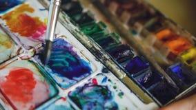 少妇艺术家与水彩油漆的凹道pictrure 在pallete的特写镜头刷子混合的颜色 股票视频