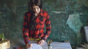 少妇艺术家在纸笔记本的绘画scetch有铅笔的在窗口看 股票视频