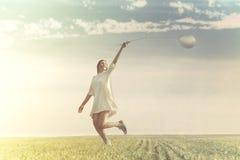 少妇获得与气球的乐趣在一个绿色草甸 图库摄影