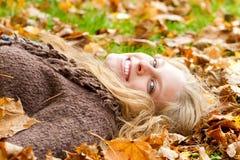 少妇获得乐趣在秋天 免版税图库摄影