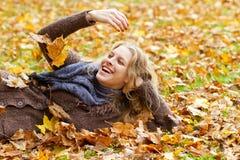 少妇获得乐趣在秋天 免版税库存照片