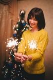 少妇藏品在她的手上闪耀在圣诞树附近 免版税库存照片