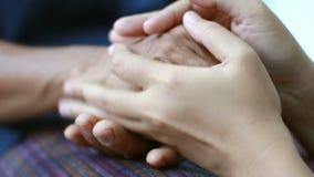 少妇藏品的手和轻拍接触到老妇人隐喻的手,并且肢体语言感觉爱的概念安慰和 影视素材