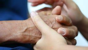 少妇藏品的手和轻拍接触到老妇人隐喻的手,并且肢体语言感觉爱的概念安慰和 股票录像