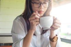 少妇装备拿着咖啡杯和喝co的白色衬衣 免版税库存图片