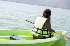 少妇装备救生衣坐的放松在船首有ped 库存照片