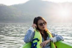 少妇装备救生衣坐的放松在船首 她看 库存图片