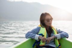 少妇装备救生衣坐的放松在船首 她看 免版税库存图片