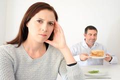 少妇让烦恼,当她的伙伴吃时和享用碳水化合物 库存图片