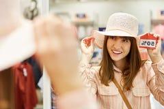 少妇试穿一个帽子,当购物时 库存照片
