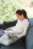 少妇读取杂志客厅长沙发 免版税库存图片