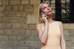 少妇谈话在她巧妙的电话,当站立在有拷贝空间墙壁的时城市街道 免版税图库摄影
