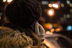 少妇谈话在手机在晚上在冬天 免版税库存图片