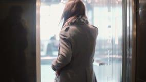 少妇谈话在智能手机,进入电梯和微笑 推力门是闭合的 股票录像