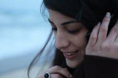 少妇谈话在电话在海旁边在冬天 免版税库存图片