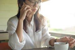 少妇谈话在电话,当拿着咖啡杯在早晨时 图库摄影