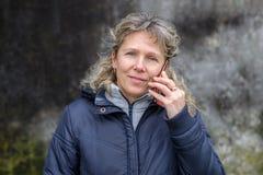 少妇谈话在街道上的一个手机 库存照片