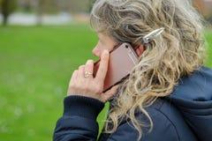少妇谈话在街道上的一个手机 库存图片