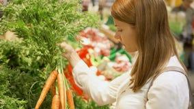 少妇购物在杂货店 站立在选择新鲜的红萝卜的菜部门 股票录像