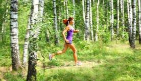 少妇赛跑者在一个绿色森林里 库存照片