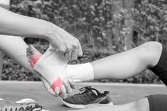 少妇赛跑者脚腕是应用的绷带由人在公园 我 库存图片
