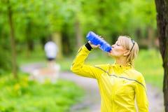少妇赛跑者饮用水 库存照片